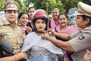 Cops giving a helmet to a woman rider as part of an awareness drive in Chandigarh on Thursday.