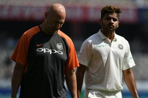 Indian cricketer Shardul Thakur (R) walks back with physio during the first day