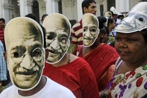 School children and teachers wearing masks of Mahatma Gandhi, the father of the nation, participate in a rally to mark the independence leader