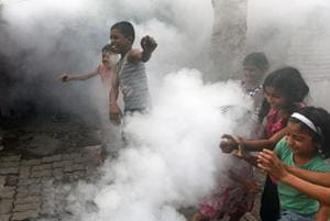 Children react during PMC worker fumigates in a slum area at Karve Nagar in Pune