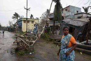 A woman stands next to a damaged communication tower after cyclone Titli hit in Srikakulam district in Andhra Pradesh, October 11, 2018.