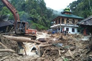 People use a heavy equipment to remove debris after flash floods hit the Saladi village in Mandailing Natal, North Sumatra on October 13, 2018.