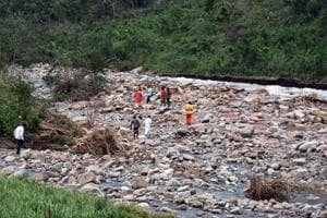 Local people watch the recovery of dead bodies at the foothill stream near Baraghar under Rayagada block of Gajapati district of Odisha, where 16 persons died in a rockslide in the aftermath cyclonic storm Titli.