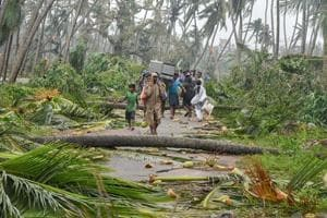A group of people relocate to safer places as Cyclone Titli hits Barua village, in Srikakulam.