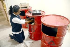 A school student puts e-waste in a drum to be reused on International E-Waste Day at Sadhu Vaswani International School Sanpada in Navi Mumbai.