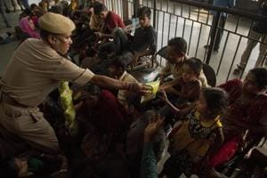 Police official distributes chips to children as suspected Bangladeshi nationals who were detained sit on a platform of a railway station in Guwahati.