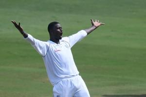 West Indies captain Jason Holder celebrates the dismissal of Indian cricketer Kuldeep Yadav during the third day