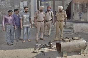 Police officials inspecting the spot where compressor blast at peepal chowk in Gaispura area in Ludhiana on Sunday.