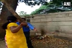 The video shows the woman dragging the man and beating him up with a stick.
