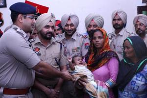 SSP Sandeep Garg hands over the child to his parents in Sangrur on Tuesday.