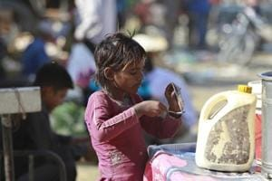 A child pours out melted ice-cream from a bowl onto a spoon on the outskirts of Jammu. Some 821 million people, or one of every nine people on the planet, suffered from hunger last year, marking the third consecutive annual increase, according to the UN's latest hunger report.