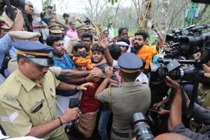 Police personnel tackling devotees protesting against the entry of women of all ages to the Sabarimala temple, at Nilakkal base camp in Pathanam, Kerala, on Tuesday.