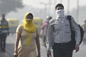 Commuters seen wearing face mask to avoid thick smog in New Delhi.