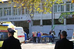 """Rescuers carry an injured victim of a blast at at a college in the city of Kerch on October 17, 2018. - Thirteen people were killed and 50 more wounded, most of them teenagers, after a blast tore into a college canteen in Russian-annexed Crimea in what Moscow called a """"terrorist"""" attack."""