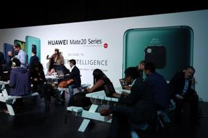 People look at display models of the Huawei Mate20 smartphone series at a launch event in London, Britain, October 16, 2018. REUTERS/Hannah McKay