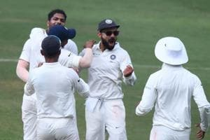 Indian captain Virat Kohli (C) and bowler Umesh Yadav (L) celebrates with teammates the fall of a wicket.