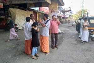 People stand around closed shops due to the 24-hour bandh at Pathanamthitta district in Kerala, on October 18, 2018.