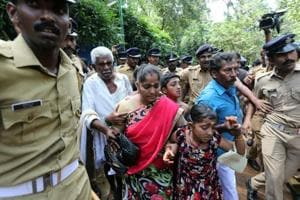 Police escort a woman and her family members after she was heckled by the protesters at Sabarimala, Kerala, October 17