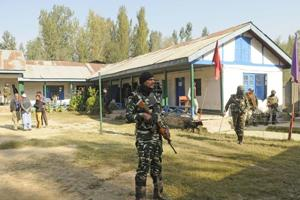 Paramilitary soldiers stand guard near outside the polling both in Hamdaniya colony area of Srinagar, Jammu and Kashmir, on Monday, October 08, 2018.
