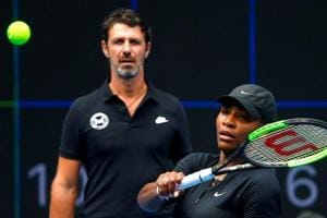 FILE PHOTO: Serena Williams of the U.S. hits a shot as her coach Patrick Mouratoglou looks on during a training session.
