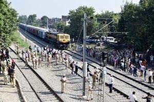 Security on high alert as a train passes by after resumption of railway services since the train accident, in Amritsar.