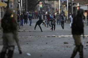 Kashmiri protesters throw stones on policemen during a protest in Srinagar, Monday, Oct. 22, 2018.