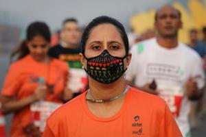 A runner wearing a face mask for protection from air pollution takes part in the Airtel Delhi Half Marathon in New Delhi.