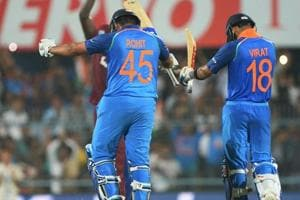Indian batsman Rohit Sharma (L) celebrates with team captain Virat Kohli (R) after completing his century during the first one day international (ODI) cricket match between India and West Indies at Barsapara Cricket Stadium in Guwahati on October 21, 2018.