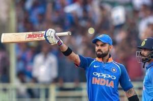 Virat Kohli raises his bat after completing 10,000 ODI runs during the second ODI match against West Indies.