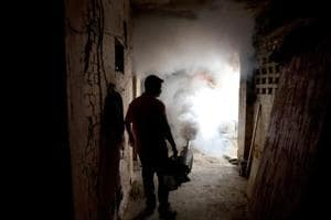 A municipal worker fumigates a residential area to check the spread of mosquito-borne diseases in New Delhi.