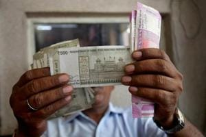 A cashier checks rupee notes inside a room at a fuel station in Ahmedabad.