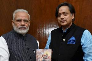 Congress MP Shashi Tharoor presents to Prime Minister Narendra Modi a copy of his book titled 'An Era of Darkness : The British Empire in India' in New Delhi on November 16, 2016.