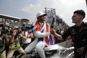 British driver Lewis Hamilton celebrates wining his fourth Formula One championship with a member of his team after the Mexican Formula One Grand Prix auto race at the Hermanos Rodriguez racetrack in Mexico City.