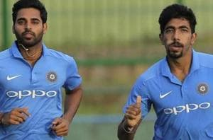 Indian cricketers Bhuvneshwar Kumar and Jasprit Bumrah jog during a practice session.