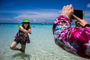 A Chinese tourist poses for a photograph in the sea at White Beach in Boracay, the Philippines.
