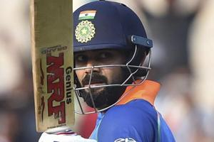 Virat Kohli raises his bat after scoring his century against West Indies.