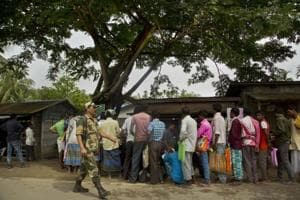 A security personnel walks past as people whose names were left out in the National Register of Citizens (NRC) draft stand to collect forms to file appeals near a NRC centre on the outskirts of Guwahati in Assam.