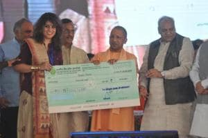 Chief minister Yogi Adityanath distributing cheques at the ODOP summit organised at Awadh Shilpgram.