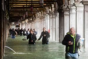 Tourists under arches next to the flooded St Mark