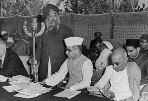 Master Tara Singh (standing) speaking at conference, with Kanyalal M Munshi (centre) and Chakravarthi Rajagopalachari (right)