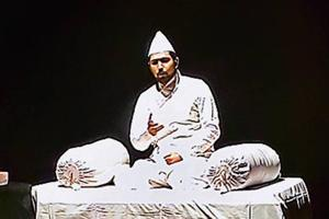 Dastango (story teller) Syed Sahil Agha seated on a white mattress, the colour matching his traditional kurta pyjama  at the event