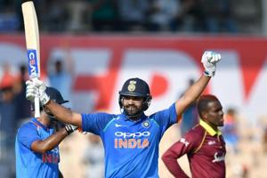 India cricketer Rohit Sharma (C) celebrates after scoring a century (100 runs) during the fourth one day international (ODI) cricket match between India and West Indies.