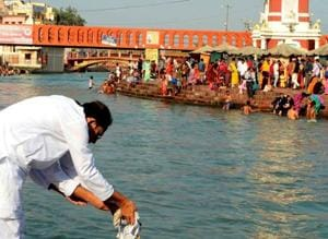A devotee immersing ashes in the Ganga at Haridwar
