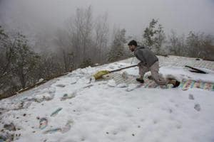 A man clears snow from the roof top of his mud-house on the out skirts of Srinagar on Sunday.
