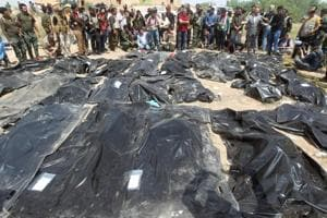 In this file photo taken on April 12, 2015, Iraqis mourn near body-bags containing the remains of people believed to have been slain by jihadists of the Islamic State (IS) group lying on the ground at the Speicher camp in the Iraqi city of Tikrit.