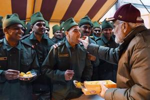 Prime Minister Narendra Modi shares sweets with army personnel.