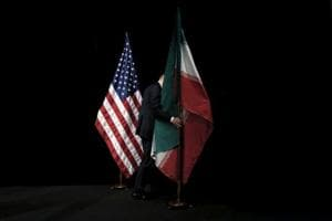 A staff member removes the Iranian flag from the stage after a group picture with foreign ministers and representatives of the US, Iran, China, Russia, Britain, Germany, France and the European Union during the Iran nuclear talks at the Vienna International Center in Vienna, Austria on July 14, 2015.