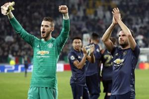 Manchester United goalkeeper David de Gea, left, and Juan Mata celebrate at the end of the Champions League group H soccer match between Juventus and Manchester United at the Allianz stadium.