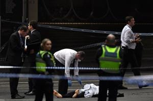 A police officer (C) inspects a body at the crime scene following a stabbing incident in Melbourne on November 9.