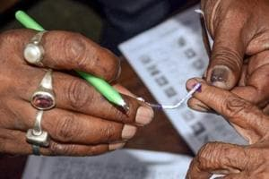 Polling officials put an ink mark on a voter